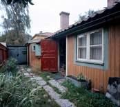 """Lindholm-Houges sista bostad på Molinsgatan i Gamla Stan, Kalmar.  Lindholm-Houge, Edvin, 1898-1969, konstnär född i Kalmar och autodidakt. L yrkesarbetade i unga år, men övergick till att helt ägna sig åt konsten. Ivan Hoflund utövade ett betydande inflytande på L under 1930-talet, liksom senare kretsen kring Axel Kargel i Sjöstugan i Borgholm. L utvecklade dock sitt eget sätt att i teckningar, lavyrer och oljemålningar skildra landskap, stadsmiljöer och interiörer. L hade sin styrka i en lyrisk kolorit att jämföra med Carl Kylberg och Karl Isaksson. Ibland talas det om """"Kalmarskolan"""", och där är L ett lysande namn i fotspåren efter Fille Fromén och Ivan Hoflund. 1941 utökar han sitt namn med Houge efter modern för att undvika förväxling med en tavelförsäljare med samma namn i Oskarshamn. L hade en mjukare penselskrift än Kargel och närmar sig stämningen kring Göteborgsmålarna, t.ex. Åke Göransson. Hans samtal blev ofta till monologer. L sägs ha sagt att två skall man vara för ett samtal, tre är redan en för mycket. L tycks ofta arbeta med tre favoritfärger: mörkrött, smaragdgrönt och violett. L:s första separatutställning dröjde till 1957 och ägde rum i Stockholm. Den fick strålande recensioner och L beskrevs som en """"intim expressionist"""". L var även en skicklig skribent som publicerade artiklar i dagspressen och några mindre skrifter. Han var till sin natur skygg och tillbakadrage, närmast en enstöring och bodde i enkla bostäder, bl.a. i ett rivningshus på Tullslätten och sist på Molinsgatan."""