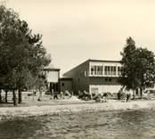 """Restaurang Slottsholmen är byggd i modernismisk stil som  karakteriseras av en avskalad och geometriskt enkel arkitektur då det är själva formerna och konstruktionen som står för det arkitektoniska värdet.  Den 15 juni 1950 brann den """"gamla"""" restaurangen ned. Den 18 november påbörjades uppförandet av den nya restaurangen, som invigdes den 17 juli 1952. För publicering av bilden hänvisas till ägaren via Kalmar läns museum"""