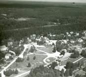 Flygfoto över Påryd. Samhället med byggnader väg och järnväg samt skog.