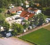 Flygfoto över del av Bäckebo. Enfamiljshus med sidobyggnad och husvagnsförsäljning