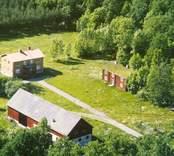 Flygfoto på en gårdsmiljö i Bäckebo. Flerfamiljshus ladugård och ekonomibyggnad.