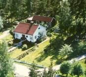 Flygfoto på enfamiljshus och sidobyggnad samt trädgård i Bäckebo.