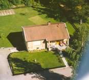Flygfoto på enfamiljshus med trädgård i Bäckebo.