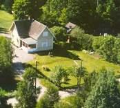 Flygfoto på enfamiljshus med tillbyggnad och trädgård i Bäckebo.