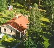 Flygfoto på ett enfamiljshus med trädgård och skogsmark i Bäckebo.