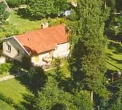 Flygfoto på enfamiljshus med trädgård och skogsmark.