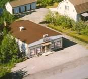 Flygfoto på ICA butiken samt ett enfamiljshus med sidobyggnad i Bäckebo.