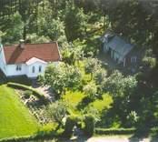 Flygfoto på ett enfamiljshus med trädgård i Bäckebo.