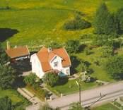 En villa, med en sidobyggnad i  trädgården.