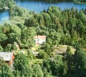 En gårdsmiljö, omgiven av skog, och med en sjö i bakgrunden.