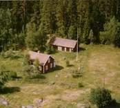 En skogstomt med en tillbyggd stuga, och uthus, i Döderhult.