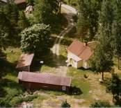 En skogstomt med en tillbyggd villa, och uthus, i Döderhult.