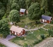 En tillbyggd stuga med trädgård och uthus, i Döderhult.