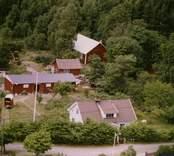 En gårdsmiljö, invid skogen, i Döderhult.