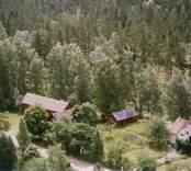 En gårdsmiljö, omgiven av skog, i Döderhult.