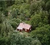 En tillbyggd stuga med uthus, i Döderhult.