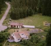 Ett boningshus med uthus och trädgård, invid skogen, i Döderhult.