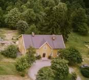 En skogstomt med en villa, och sidobyggnad.