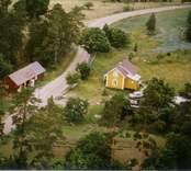 En tillbyggd stuga med trädgård och uthus.