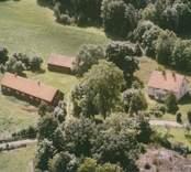Bostadshus och ekonomibyggnader vid åkermarker i Madesjö.