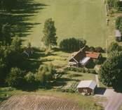 Ett bostadshus med trädgård vid åkermarker i Sankt Sigfrids socken.