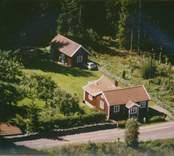 Enkelstuga med tillbyggnad och uthus på tomten i Madesjö socken.
