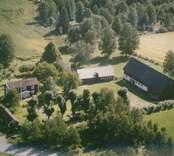 Bostadshus och ekonomibyggnad vid åkermarker i Madesjö socken.