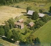 Bostadshus med sidobyggnader och ekonomibyggnad vid åkermarker i Madesjö socken.
