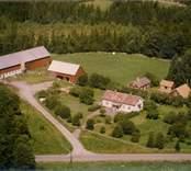 En vit parstuga, bostadshus och ekonomibyggnader i Madesjö socken.
