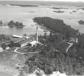 Flygfoto över Figeholm. Industri med skogen och Östersjön intill.