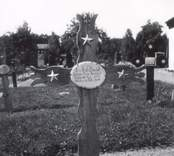 Ett gravkors i trä på Hjorteds kyrkas kyrkogård.