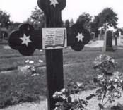 Ett gravkors i trä på kyrkogården vid Hjorteds kyrka.