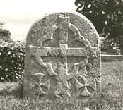 Två gavelhällar av röd kalksten, ursprungligen från en gravvård från 1200-talet.