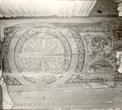 Östra flygeln. Del av paneltak med målad ornering i karolinsk barockstil, uppsatt i sekundärt läge i rummet till vänster om förstugan