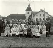 Klassfoto av årskurserna 3 och fyra framför kyrkan och skolan i Hjorted.