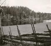 Landskap i Hjorted. En sjö och en gärdsgård i förgrunden.