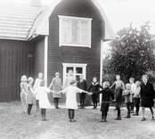 Skolbarnen och lärarinnan Ester Fransson utanför skolan år 1928.