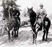 Två selade hästar med varsin herre som rider barbacka.
