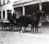 Framför huvudbyggnaden står en liten vagn dragen av parhästar. På kuskbocken sitter en kusk i uniform och en herre.