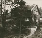 """""""Arkitekt Olssons hus, Rh"""", [stadsarkitekt J Fred Olssons sommarvilla i Rinkabyholm, nuvarande Mandelblomsvägen 38, Hossmo socken]. Fotografi på brun kartong; 16 x 11 resp 21 x 16 cm. Fotograf troligen C G Rosenberg 1917."""