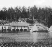 """År 1890 köpte badstyrelsen kallbadhuset vid """"Gröna plätten"""" för 450 kronor. 1893 uppförde badbolaget, på samma plats, ett nytt kallbadhus med skilda avdelningar för damer och herrar. Joelsjön eller Kvarneslättsgölen hade nu börjat kallas Linnéasjön. Sommaren 1902 byggde man om och moderniserade det lilla kallbadhuset. 1912 flyttades det till norra sidan av sjön, genom att på vintern dra det över isen. Badhuset genomgick våren 1922 en fullständig reparation och bilden är från detta år. Vilka var ägarna till segelbåtarna? Dessa bilder är tryckta i almanackor utgivna av Nybro Hembygdsförening. De är inte till salu genom KLM, men vi väljer att visa dem då vi har få bilder från det Nybro var en gång."""