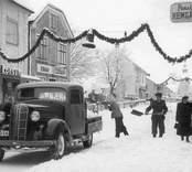 Månadens bild är från november 1951. Vid den julpyntade Storgatan arbetar Einar Johansson och medhjälpare i Alltjänst med snöröjning. Vi ser de butiker, som då fanns i kvarteret Balder. Alltjänst hade sitt kontor bakom Cedmerts butik och verkstad. I fastigheten bortom Hemgården fanns Varuhuset Resia. Dessa bilder är tryckta i almanackor utgivna av Nybro Hembygdsförening. De är inte till salu genom KLM, men vi väljer att visa dem då vi har få bilder från det Nybro var en gång.