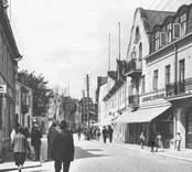 """J.E. Peterssons Färghandel etablerades 1901. Han efterträddes av sonen Simon, som 1931 sålde rörelsen till Folke Eriksson: Ljungdahls drev bokhandeln vid Storgatan fram till 1937, då den togs över av Lars Bohman. Notera den ambulerande """"fiskaffären"""" i bildens nedre högra hörn. Bilden från cirka 1930. Dessa bilder är tryckta i almanackor utgivna av Nybro Hembygdsförening. De är inte till salu genom KLM, men vi väljer att visa dem då vi har få bilder från det Nybro var en gång."""