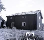 Boningshus med en brunn i förgrunden.