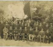Gruppbild med fackföreningsfana. Kalmar hamn och stuveriarbetare är samlade för en gruppbild. Tredje från höger, med X över hatten är hamnarbetare Gustaf Henrik Isaksson, Kalmar.