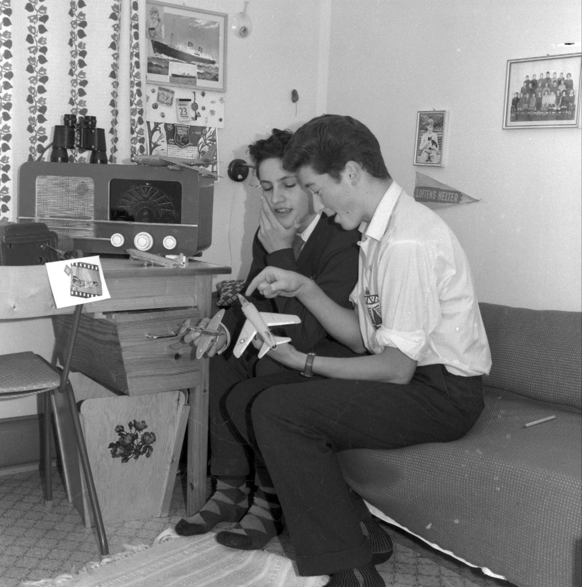 Arne Moe og Tormod E. Eitrheim studerer modellfly på gutterommet. Bord med skuffe, radio, kikkert, papirkorg av finér (laga på sløyden) kombinert seng og sittebenk røyrstol,  på veggen: klassefoto, kalender, timeplan, gardin (Foto/Photo)
