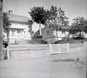 Vy från Figeholm, bostadshus med träpanel och valmat sadeltak. Gata och staket.