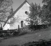 Döderhults kyrka med stenmuren i förgrunden.