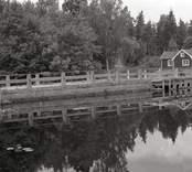 Bro över Hagbyån nordost om Strömsholm i Nybro kommun. Foto, uppströms vid dammen. Broarna 33-81 och 32-81 från nordost.