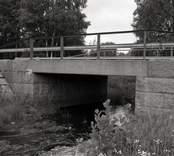Bro över Gullaskruvsjöns utlopp vid Flygfors i Nybro kommun. Foto, nedströms från öster.